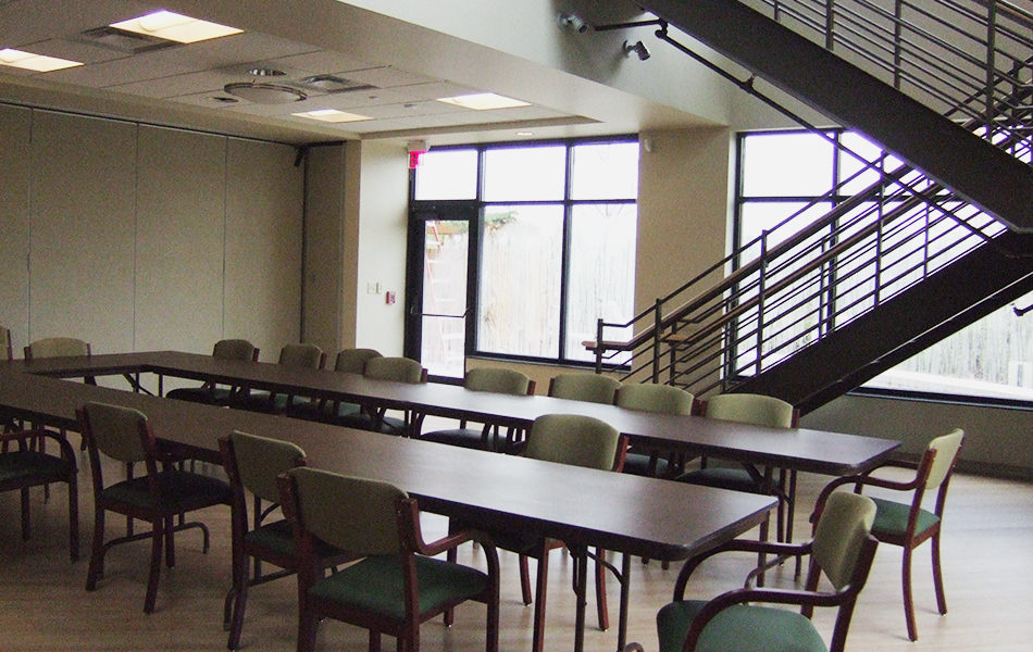A meeting space at Rockdale Temple. One wall is full of windows. A large staircase is against the wall of windows and leads up to a second floor The room contains long brown tables with many wooden chairs with light green padded backs and dark green padded seats.