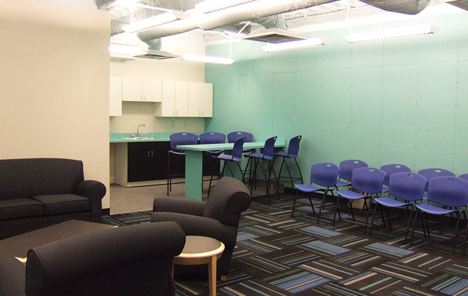 Lounge at Rockdale Temple. A seating area with a dark brown sofa and arm chairs around a coffee table is to the left. To the right are bright purple stackable chairs in rows. Int he back is a small kitchenette with a sink, a few cabinets, and a teal bar extending out from the far wall, the same color teal as the bar and counter. Six purple stackable tall chairs line the bar, three on either side.