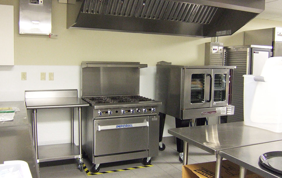 The updated kitchen for Rockdale Temple. A six-burner, stainless steel stove is center, and to the right is a holding cabinet. Lots of stainless steel counters can be seen.