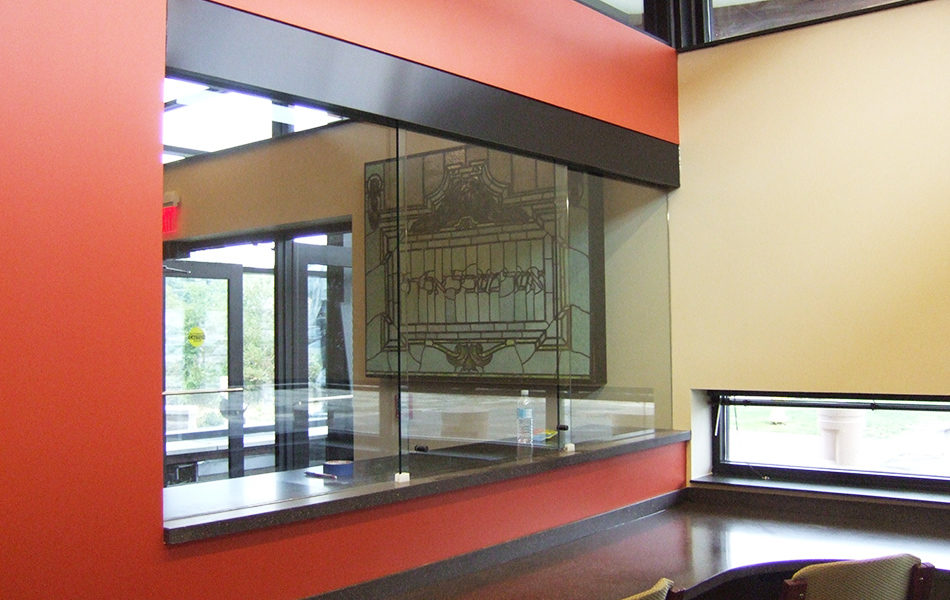 A new common space at Rockdale Temple. Chairs are tucked into counter along the wall of a work space. One wall features a glass section, allowing those in the work space to see into the foyer. Just past the glass section can be seen a stained glass window featuring Hebrew script is on display in a case and hanging on the wall.