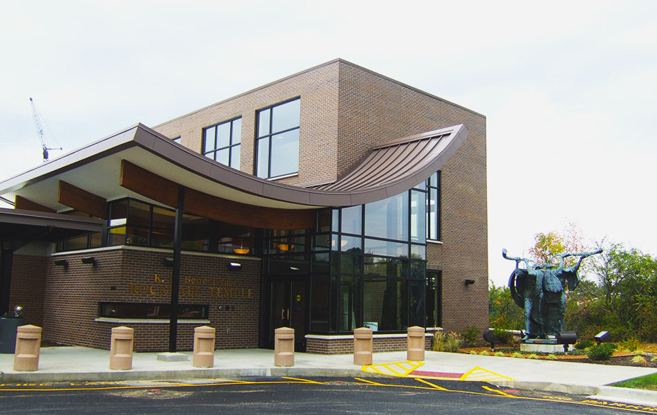 The exterior of the main entrance to Rockdale Temple. The building is brown brick. The roof of the foyer is a eye-catching U shape, sloping down to the door, then curving back up as it extends out to cover the outdoor entry way. The foyer is all glass. Large cement bollards line the curb, painted beige. To the right is a large sculpture of figures playing instruments surrounded by a small garden of shrubs. Trees and plants are in the background.