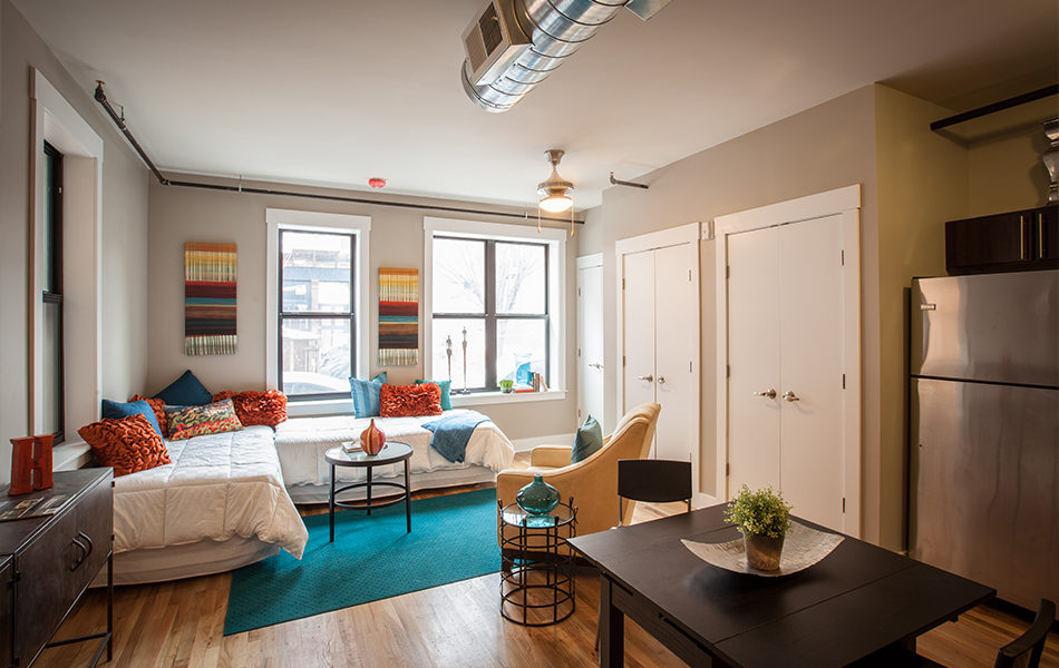 A cozy studio apartment. Two twin beds are tucked in the corner with white bed spreads and vibrant colored and patterned throw pillows. A pale yellow arm chair is in the center of the room facing the beds. Two small round tables with metal supports and glass tops accompany the furniture. There are two large windows on the far wall, allowing lots of natural light. A small table with seating for two can be seen in the bottom right corner, with a decorative plant in the center. Closet doors line the far right wall. The walls are taupe. An exposed duct is on the ceiling. To the far right is a stainless steel refrigerator. A bright teal rug is in the center of the room.