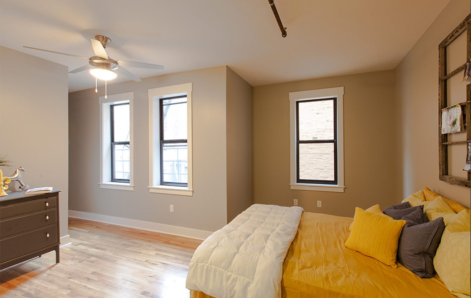 Bedroom of Republic Lofts Apartments. Queen bed with bright yellow bedding hugs the right wall. Hardwood floors and three windows letting in natural light. A ceiling fan and light hangs from the ceiling at the left side of the room. A small dresser is against the left wall. The walls are painted a neutral taupe.