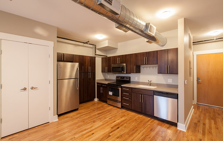 The interior of an unfurnished studio apartment, focusing on the kitchen. The far left wall has two sets of double doors, painted white and ostensibly leading to closets. The kitchenette tucks into the corner, with a stainless steel refrigerator to the left surrounded by dark wood cabinets. The right side features more dark wood cabinets and drawers and stainless steel microwave, stove, and dishwasher. An exposed duct is on the ceiling, there are hardwood floors throughout.
