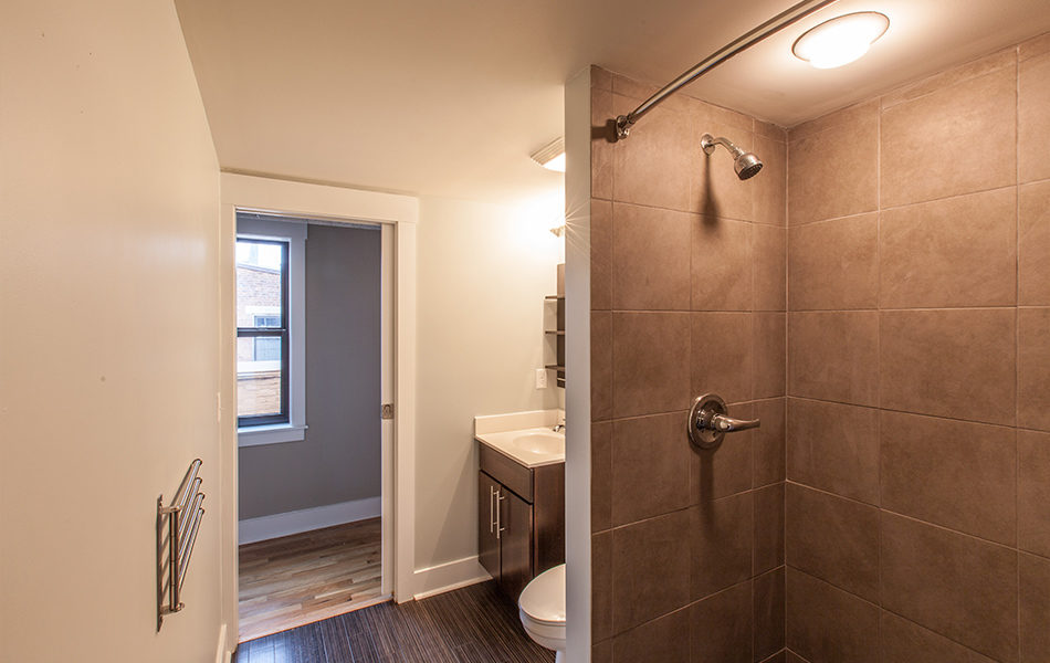 A bathroom. The shower is to the right, with now shower curtain. The shower is lined with large square stone tiles, and a light above. Just past the shower is a toiler and a single sink with a dark wood cabinet. The floor looks like dark hard wood. The door leads to a hall with lighter hard wood floors, a window letting in natural light. The door to the bathroom is a pocket door.