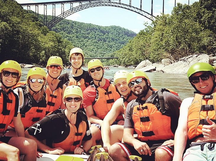 Group of HGC employees smiling while whitewater rafting