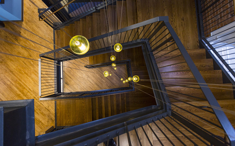 A view looking down a three-story wooden staircase with steel railings. The staircase makes a rectangular shape as it twists downward. The wood is plain-sawn white oak, laminated. Lights dangle through the center of the stairs, appearing as sparkling golden-yellow orbs.
