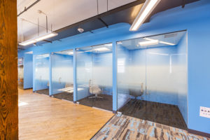 A blue wall with four glass doors leading into private phone call spaces as part of a modern office space. The rooms have dark gray carpet, and each room has a chair and an outlet. The right side of the hallway has a brightly pattern carpet, which ends and begins a hard wood floor hallway. A wood beam frames the left side of the image. Fluorescent lighting hangs from a high, white ceiling.