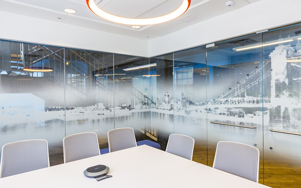 A conference room. The room is enclosed by glass walls, but the glass has the Cincinnati skyline imprinted on it in a white-scale color scheme. The conference table is large and square, with cool gray chairs pushed in. A circular light with orange accent casing hangs from the white ceiling. A large staircase can be seen beyond the conference room walls.
