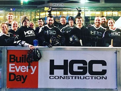 Team of athletes stand behind HGC Construction sign