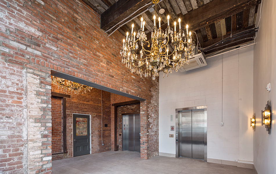 The lobby of a renovated building. Exposed brick walls and aged wooden ceilings show the building's history, but two brad-new elevators are at the far wall, and two grand chandeliers hang from the ceilings.