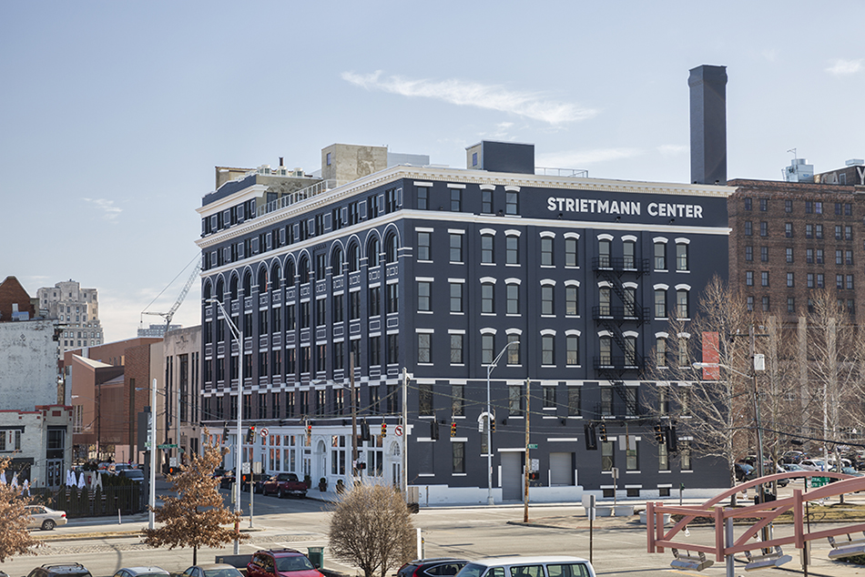 The Strietmann Center. A large, historic building at the corner of a mid-sized city intersection. The building is brick, painted a dark blue-gray. There are six stories, each either lots of windows. The windows have white stone above it. The sky is blue with one wisp of a cloud above the building.