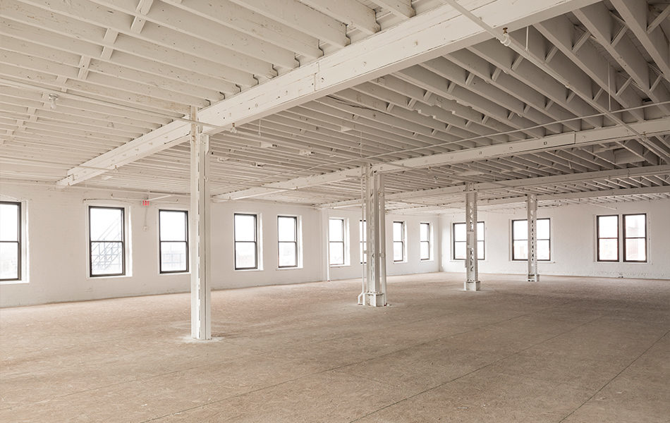 A renovated but unfinished space in a large historic building, a former factory. The far wall and left wall are lined with large windows. Steel columns cross the middle of the room. Ceiling beams are exposed, but painted a clean white.