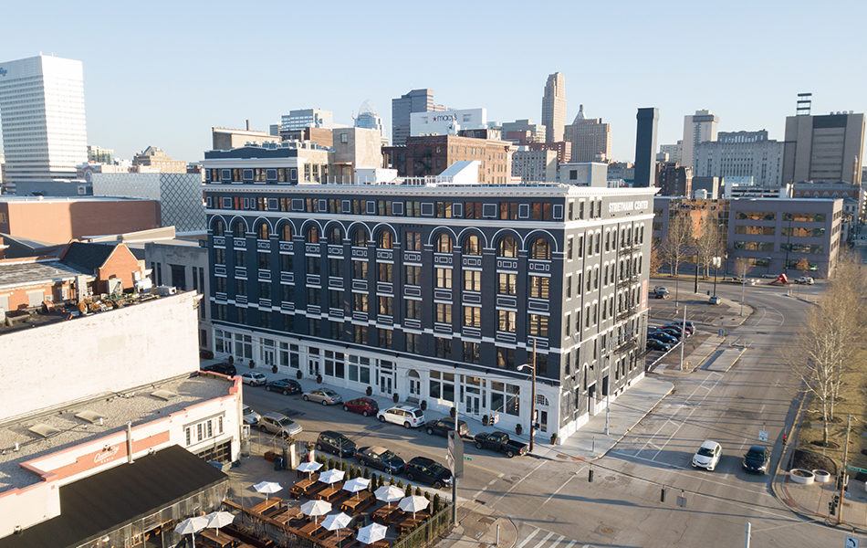 A low aerial view of the Strietmann Center, with the skyline of Cincinnati in the distance. A large, historic building at the corner of a mid-sized city intersection. The building is brick, painted a dark blue-gray, except for the street-level. At the street level, the South side has lots of windows and storefront entrances is painted white, while the East side has having smaller windows and only one entrance is the blue-gray painted brick. There are six stories, each with lots of windows. The windows have white stone above it. The sky is pale blue, with the cool light of sunrise illuminating the East-facing wall of the building.