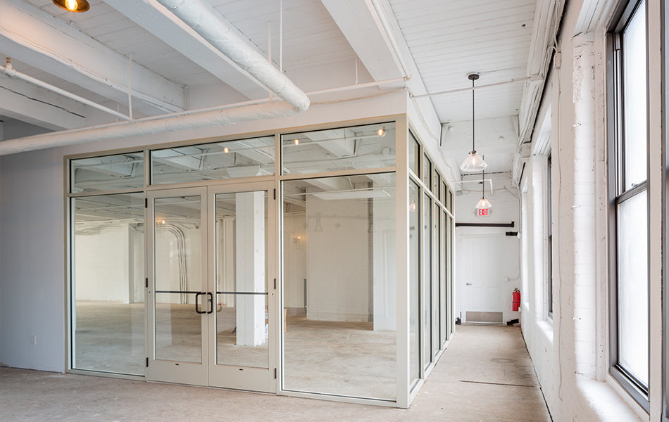 Potential office space in a newly renovated building, originally an historic factory. Painted all white, a hallway runs along the window-filled exterior wall to the right. To the left is a room, framed by glass walls to let in the natural light. Double doors face the camera, as the hallway continues left off camera.