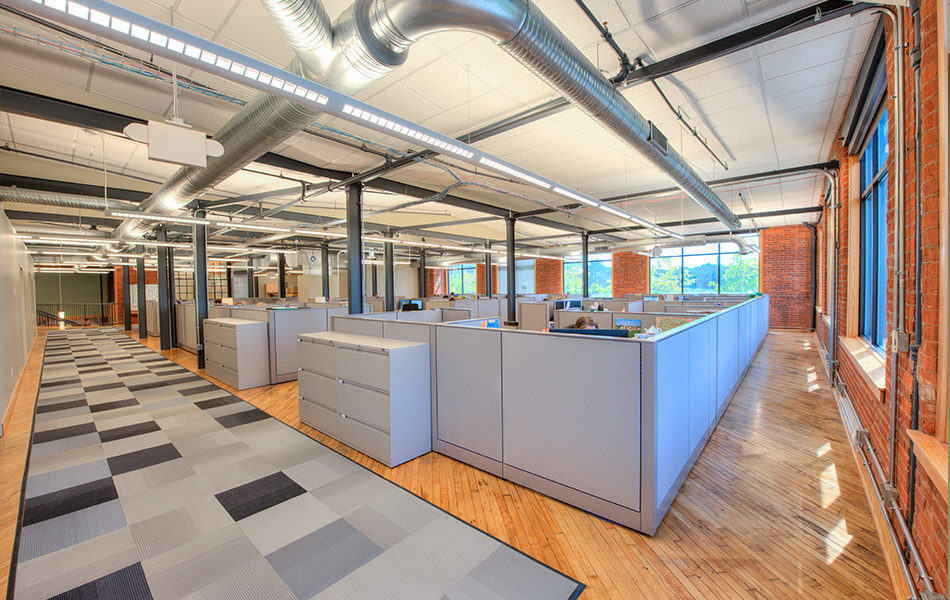 An open office space. A cluster of cubicles are centered in a large open space with hardwood floors. Gray checkered rugs mark the walkway around the cubicle space. The back walls have large windows, looking out on green wooded space. The exterior walls are exposed red brick and the window frames are rustic wood. The ceiling displays exposed ducts. Support beams throughout the room are black. Fluorescent lighting illuminates the bright space.