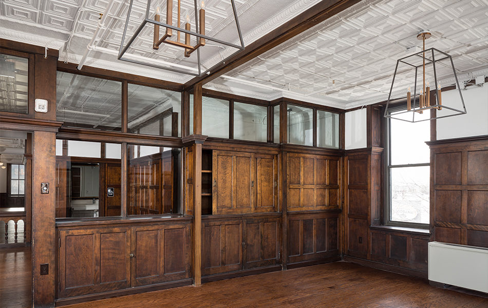 A potential conference room with dark wood paneling, renovated from an historic factory. The far wall features built-in cabinetry, and the top row of paneling has been replaced with glass to let light pour through the building. The ceiling is painted white and features crown molding. The floors are a dark wood to match the panels on the walls.