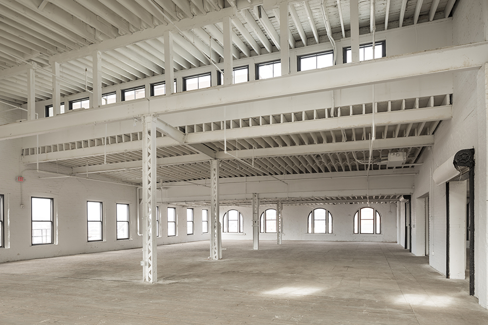 A renovated but unfinished space in a large historic building, a former factory. Large doorways with overhead doors are along the right wall. The far wall and left wall are lined with large windows. Steel columns cross the middle of the room. Ceiling beams are exposed, but painted a clean white.