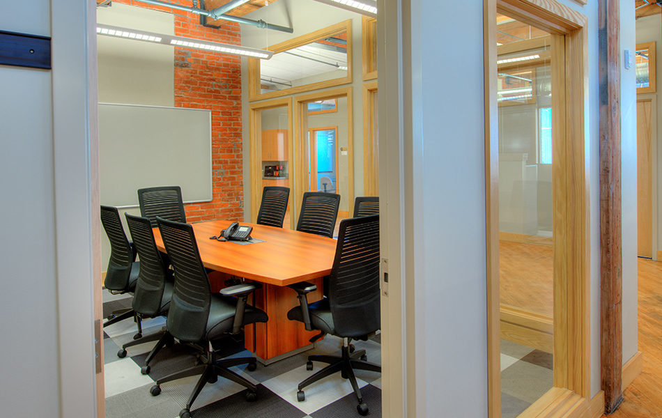 A small conference room. The walls are windowed, making the space feel bigger and brighter. A wooden conference table with one phone in the center takes up most of the room. Eight large black office chairs surround the table. A dry erase board is on the far wall, which shows some exposed red brick. Gray checkered rug covers the floor. The windows are framed in light wood, and the walls are a very pale gray, almost white.