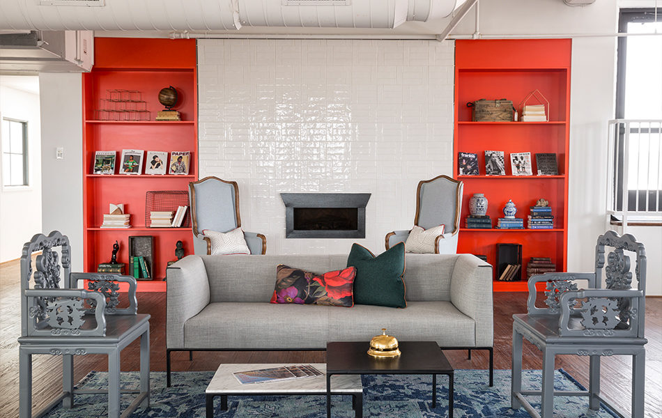 A vibrant, modern sitting area. The far wall holds a small fireplace tucked into a white painted brick wall, with bright red floor-to-ceiling bookshelves on either side. Two high-backed arm chairs in a soft sky blue sit to either side of the fireplace. A long, gray sofa faces the camera. Two throw pillows sit in the middle of the couch. Two ornately carved chairs, which were painted gray in this renovation, are on either side of the sofa. Two coffee tables are in the center, with a bellhop bell and some pamphlets. A decoratively patterned blue rug is under the couch and carved chairs.