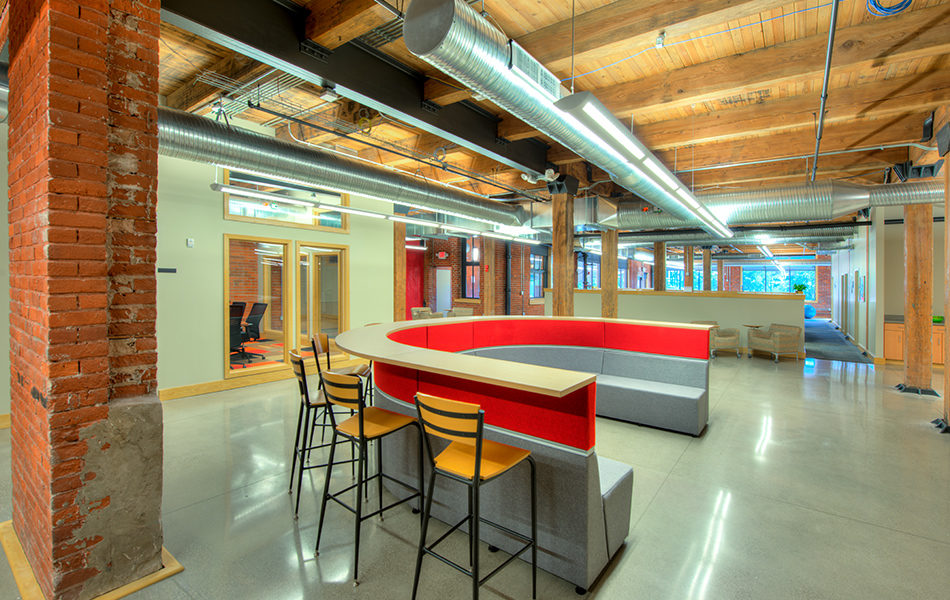 An open office space, mixing the aesthetics of modern and rustic. A large U-shaped piece of furniture is in the center. The inside is upholstered in gray and red and serves as a bench, the top has a shelf extending around it, allowing the piece of furniture to double as a bar. Tall goldenrod stools sit around the bar. In the distance are beige arm chairs, wooden support beans, and lots of windows.
