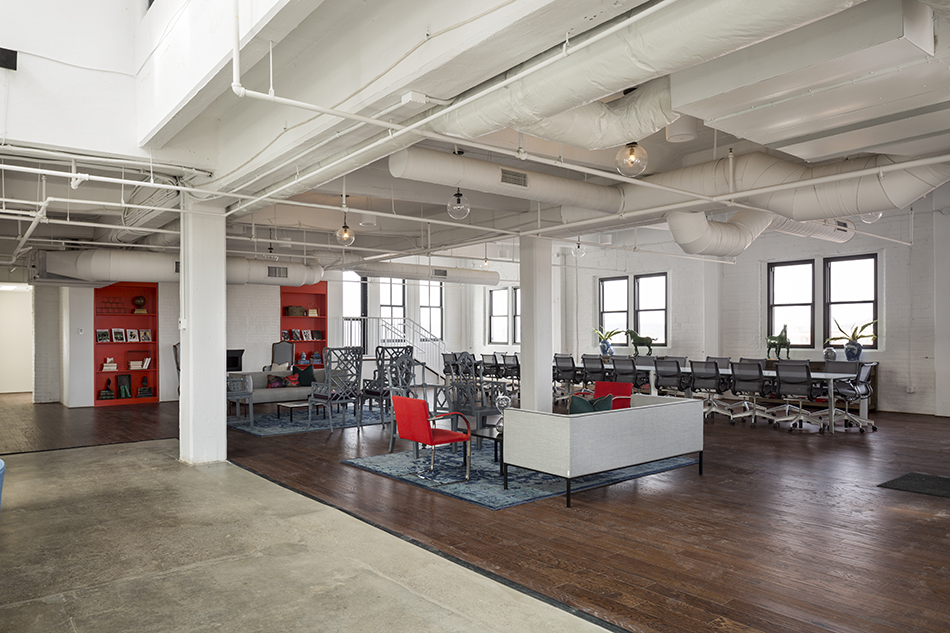 A large, modern, corporate gathering space. The far left wall holds two bright red book shelves, and a sitting area. A second sitting area is closer to the camera. An extremely long conference table lines the far right wall, with rolling desk chairs tucked in. Most of the floor is hardwood, except for a section to the left which is cement. There are lots of windows, and almost everything is white, including walls, ceilings,exposed duct work, and columns.