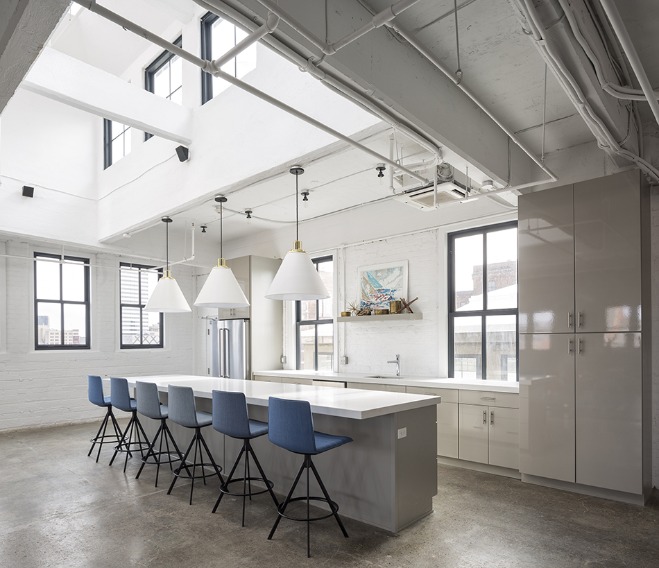 A very clean and chic modern kitchen. The walls, ceilings, counters, lighting, and cabinets are all very white. Lots of windows let in cool light. Six tall blue chairs are at the bar. A shelf over the sing holds rustic knick knacks and a colorful painting.