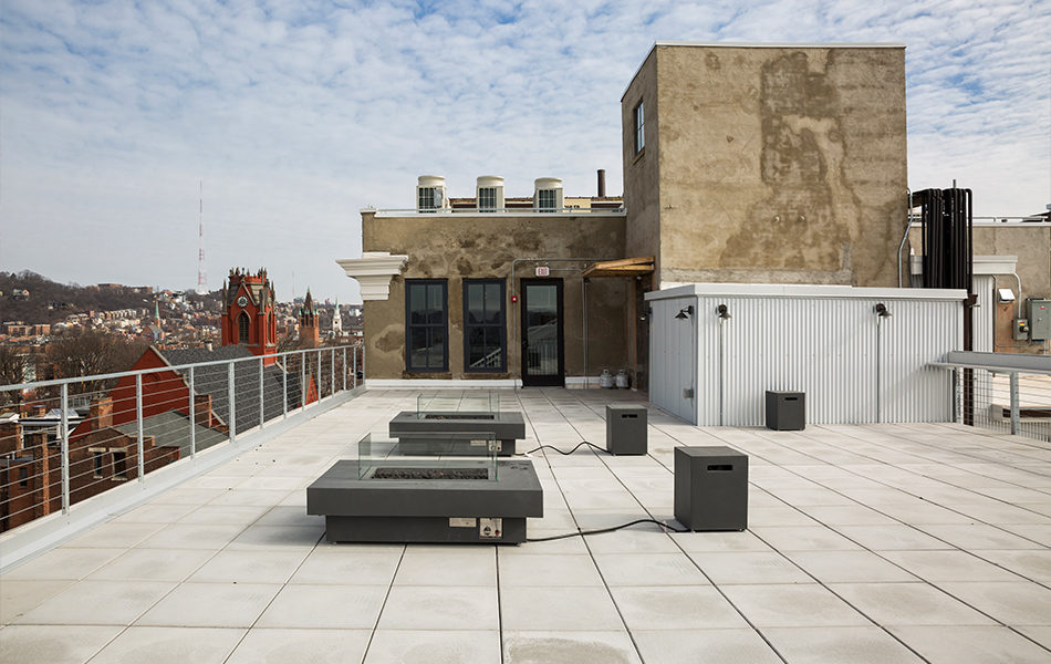 The rooftop deck of a building, with two square electric fire pits surrounded by bench seating. The entrance to the roof top is in the background, a cement structure with new, tall windows and a glass door. A view of a city beyond the railing to the left. Blue skies peek through a cottony layer of clouds.