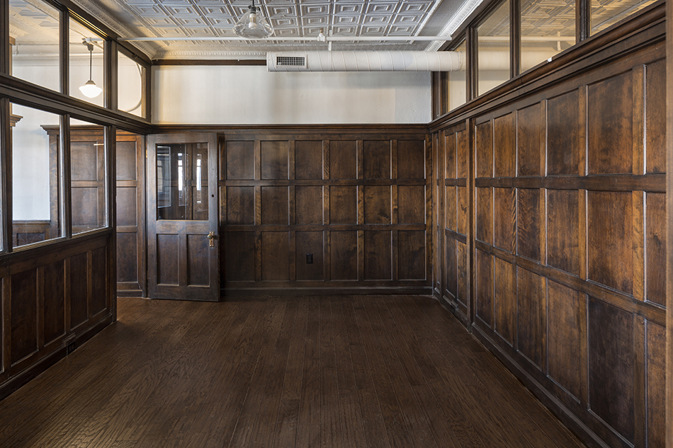 A potential conference room with dark wood paneling. The left wall has windows looking into the hall and letting in light. The door has a large window, and is propped ajar. The ceiling is painted white and features crown molding. The ducts are exposed, but painted white to blend in with the ceiling. The floors are a dark wood to match the panels on the walls.