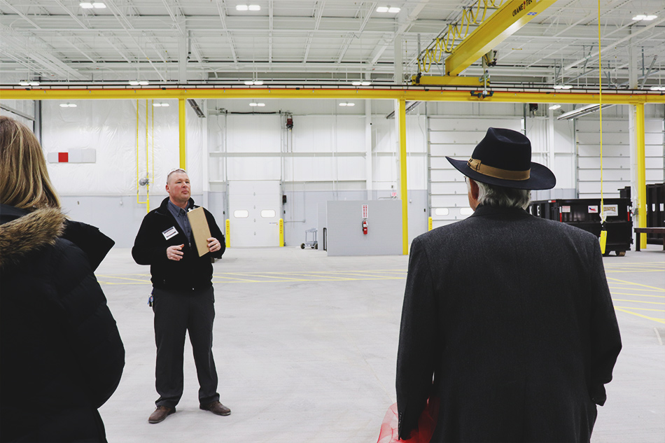 An adult male with light skin and closely shaved brown hair stands, wearing black pants and a black zip-up sweater is standing in a large warehouse. The warehouse is predominantly gray, but beams, cranes, and walkways are painted bright yellow. The man is holding a clipboard and addressing two people who are standing in the foreground and facing away from the camera.