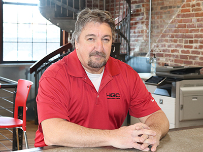 Greg Penvose. A middle-aged man with broad shoulders, light skin, salt-and-pepper graying soft hair and a goatee. He is gazing at the camera with a small, closed-mouth smile. He wears a red polo shirt, with a white undershirt showing at the neckline, and the HGC Construction logo embroidered on the left breast of the shirt. His hands are folded in front of him and resting on a concrete bar. Behind him is a spiral staircase, a copy machine, a brick wall, and a large window letting in cool light.