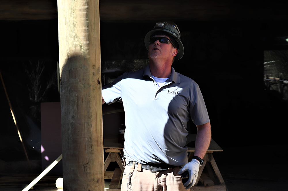 A construction worker faces the camera but is looking up to the top of a large wooden support post. The worker is wearing a hard hat with a head lamp, dark protective eyewear, and a gray short-sleeved polo shirt with a white undershirt showing at the neck. The shirt is embroidered with the HGC logo over the left breast. He is also wearing work gloves, and a watch on his left wrist.