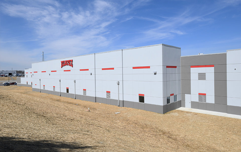 The exterior of the new Rumpke repair facility. A large gray, rectangular building. Small square windows line the first story. Accents of red are on the wall. The Rumpke logo is displayed, centered on the top of the building. The ground around the building is covered with hay, and the sky is blue with wispy clouds.