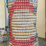 "A structure built out of canned goods. The structure is made to look like a large beer stein, with the pattern of the Cincinnati city flag, including a large red ""C."" There are cans of black beans, potatoes, coffee, tuna, diced tomatoes, and bags of marshmallows."