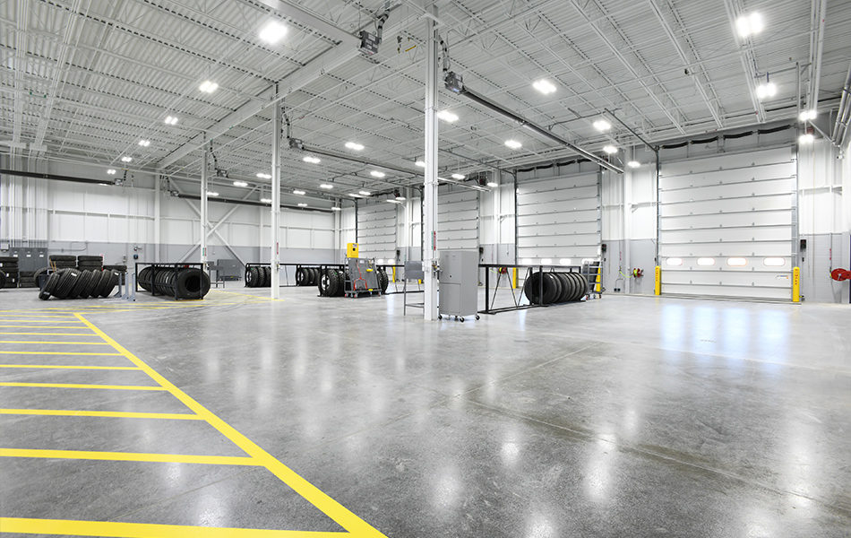 A large industrial garage for repairing trash and recycling trucks. The entire facility is very gray, with cement floors and corrugated metal roofing. Fluorescent lighting. Yellow stripes indicate the pedestrian walkways within the facility, and tires are stored in racks throughout the large and open room. Four garage doors line the far wall.