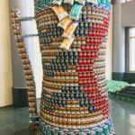 A structure built out of canned goods. The structure is made to look like a large beer stein, with the pattern of the Cincinnati city flag. There are cans of black beans, potatoes, coffee, tuna, diced tomatoes, and bags of marshmallows.