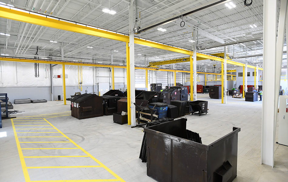 A large industrial garage for repairing trash and recycling trucks. The entire facility is very gray, with cement floors and corrugated metal roofing. Fluorescent lighting. A pedestrian walkway, painted yellow on the floor, heads to the left of the frame and then turns to the right. Large brown dumpsters are placed throughout the warehouse space, to be cleaned or repaired.