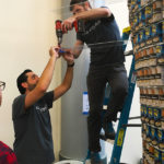 Two young men, both with light skin, dark hair and facial hair, are building a structure out of canned goods. One man stands on a blue ladder and holds a red drill, while the man standing on the ground helps to hold the piece of plastic that the man on the ladder is drilling.