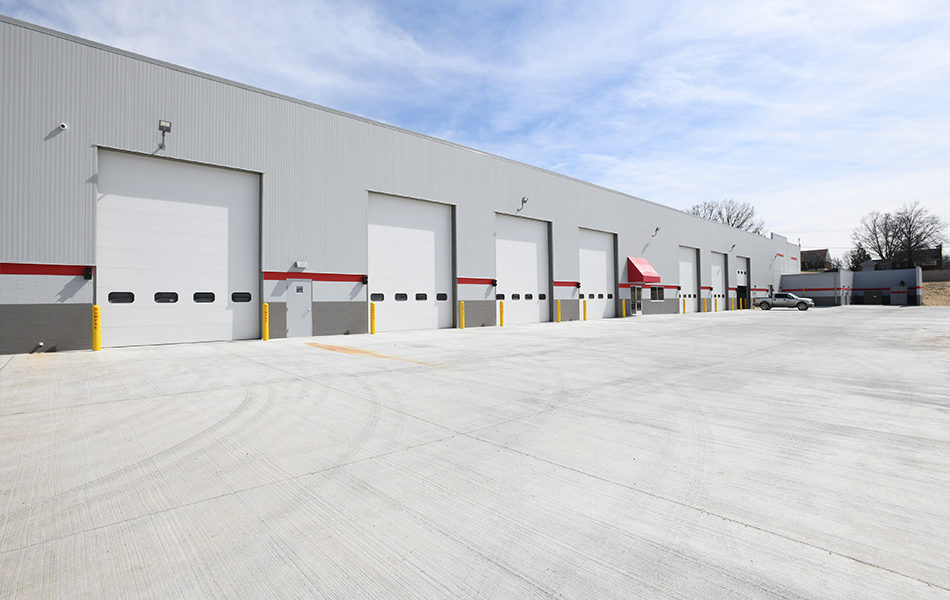 The exterior of the new Rumpke truck repair facility. The building is gray. A dark gray border lines the bottom, a red strip crosses the lower midsection of the building, and the upper section is light gray. Seven large closed garage doors with small windows line the building. The eighth, farthest in the distance, is half open and a chrome pick up truck sits in front of it.