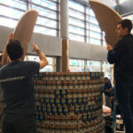Three young men work together to assemble a construction made out of canned goods. To the left, one man is holding a piece of cardboard above his head. The man in the foreground, facing away from the camera, is extending his arms to help move that same piece of cardboard. To the right, one more young man is facing two-thirds away from the camera, standing on a blue step ladder, holding a similar piece of cardboard and watching the other two. The event is taking place in a large room with high ceilings and lots of windows.