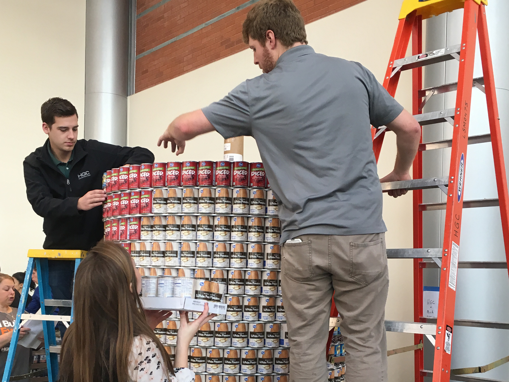 Three people are assembling a cylindrical structure out of canned goods. Farthest away and to the left of the image is a young man with a tan complexion and short, black hair. He is standing on a small blue ladder and arranging cans of diced tomatoes at the top of the structure. In the middle, standing on the ground, and facing away from the camera, is a young woman with light skin and long, straight brown hair with honey highlights. She is holding a tray of canned potatoes. To the right, facing away from the camera and standing on a large orange ladder, is a young man with light skin, short brown hair and a beard. He is reaching out to adjust the top row of canned tomatoes.