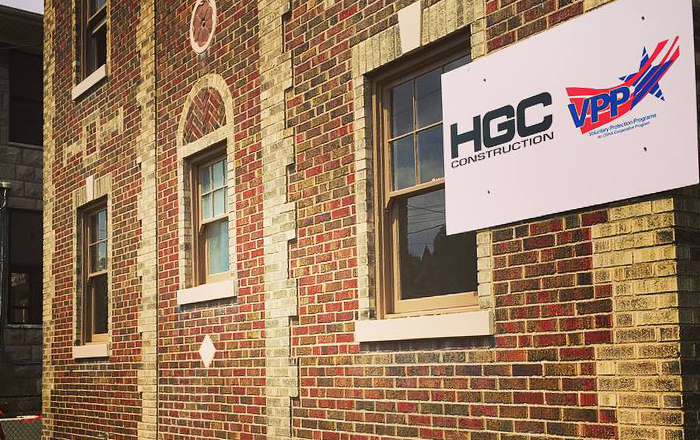 A building, with mainly red brick and some gray brick creating decorative patterns. Windows, framed by gray brick. A sign hangs on the wall in the top right corner of the picture, displaying the HGC Construction logo and the Voluntary Protection Programs logo.