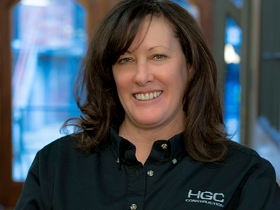 Kim Hoffa. A middle-aged woman with light skin, hazel eyes, and wavy, shoulder-length brown hair with side-swept bangs brushed to her right side. She is wearing a black button-down shirt with the HGC Construction logo near the left shoulder and smiling. Windows are out of focus in the background.