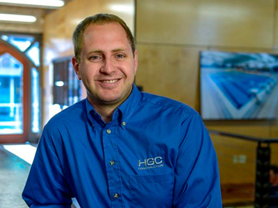 Kevin Gilbert. A middle-aged man of average build with light skin, blue eyes, and light brown hair. He is wearing a bright blue collared and buttoned-down shirt with the HGC logo embroidered over his left breast, and he is smiling. The background is an office environment with a light-filled glass door over his right shoulder, and a large photo print of a pool hanging on the wall over his left shoulder.