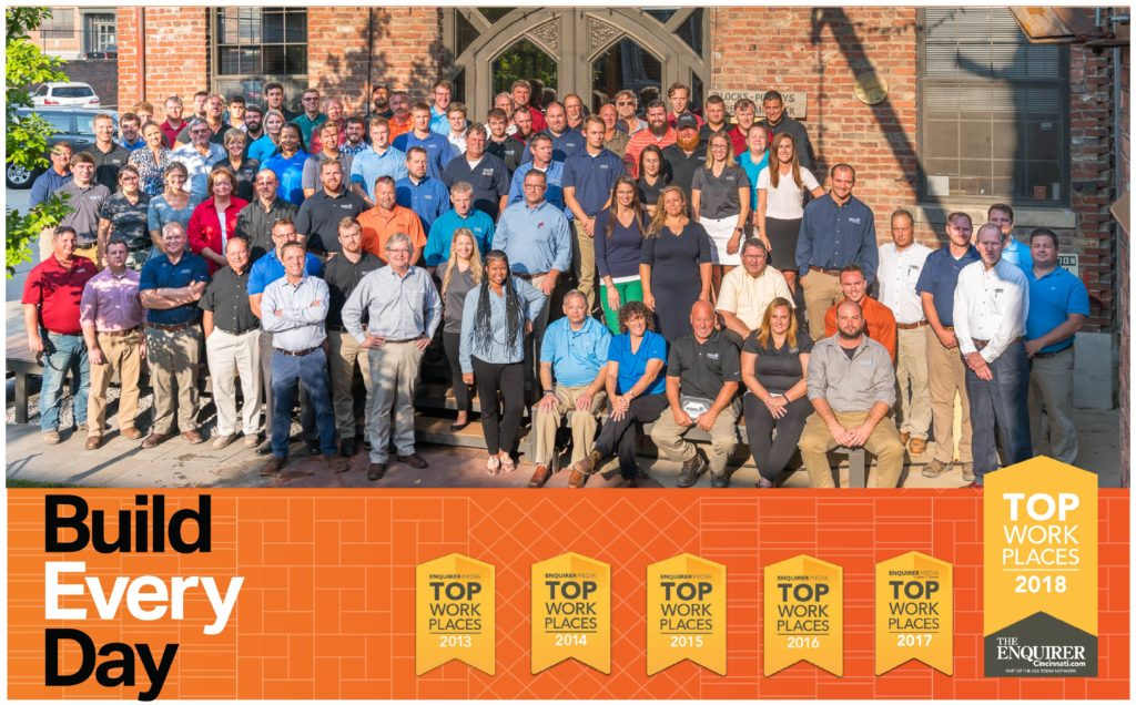 More than fifty HGC employees, diverse range of age, gender, and race, standing outside and smiling, with a banner displaying history of Top Workplace awards, including Top Workplace 2018