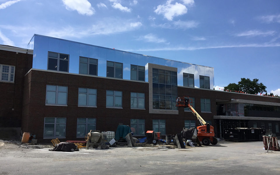 A modern three-story red brick school building, Amity Elementary, under construction with large equipment in front. A sunny day with blue sky and wispy clouds.