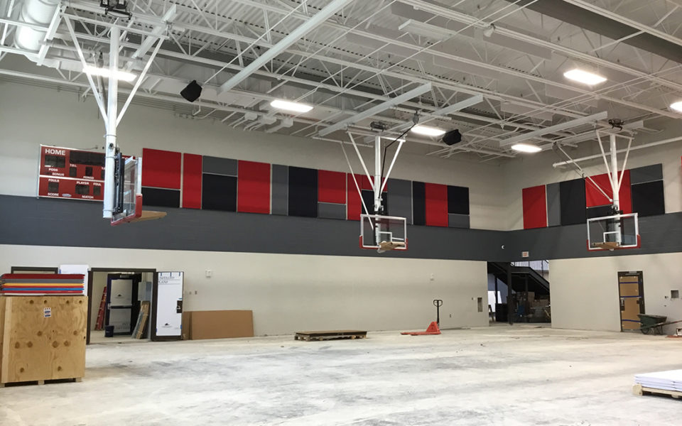A school gymnasium under construction at Amity Elementary. The floor is unfinished and dusty, but the basketball hoops are installed and red gray and black wall padding adorns the walls.