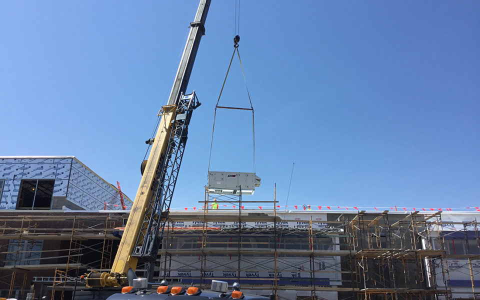 A large yellow crane lifts a hefty HVAC machine onto the roof of the new addition for Amity Elementary. The front of the building is covered in construction scaffolding, and the top of a truck can be seen in the nearest foreground. The sky is blue with not a cloud to be seen.