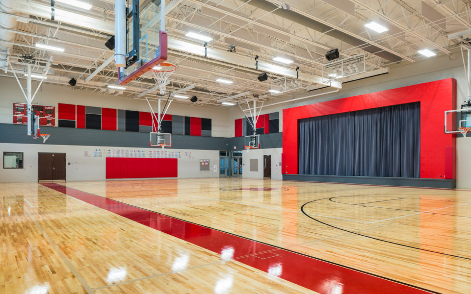 A newly renovated gymnasium. The floors gleam, the far right wall has a large expanse of curtains leading to the new stage area. Basketballs hoops hang from the ceiling. The ceiling is white, with lots of fluorescent lighting. The accent colors are predominantly red, with some gray and black.