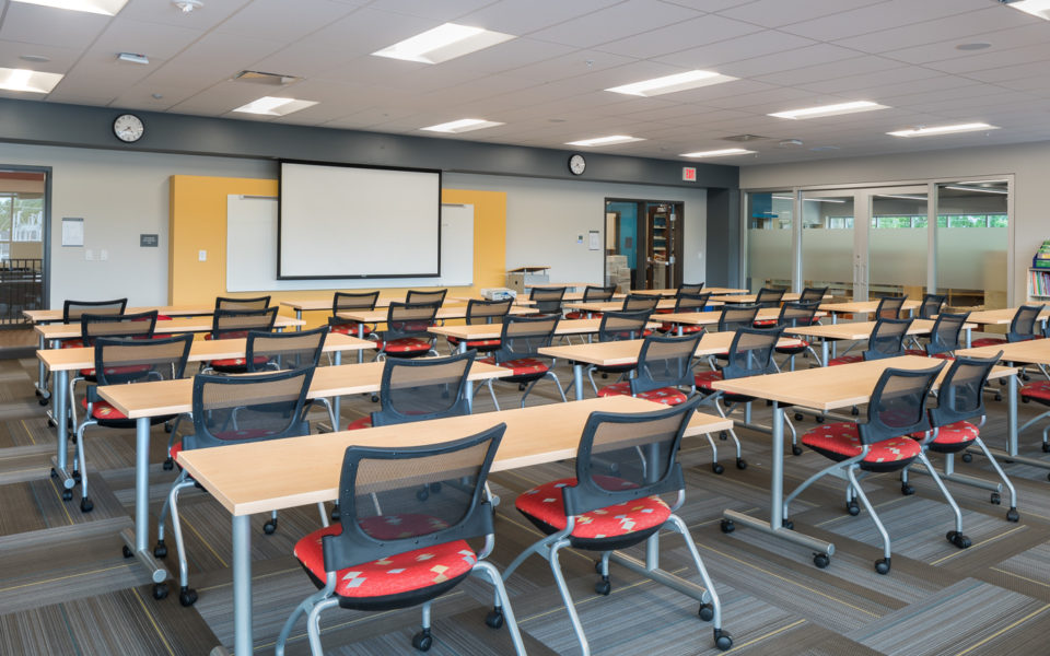 A large classroom, seen from the back of the room. Four rows of tables span the classroom, and each table has two rolling chairs with bright red patterned upholstered cushions tucked beneath the table. The front of the classroom has an accent of yellow, and a whiteboard on display. This room is for teachers professional development.